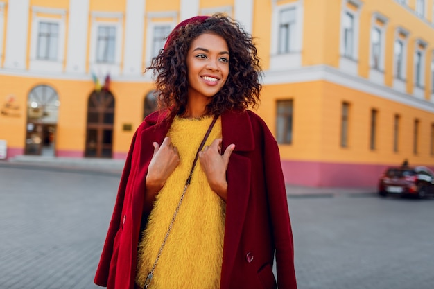 Modieus meisje in geweldige winter outfit en accessoires poseren op geel