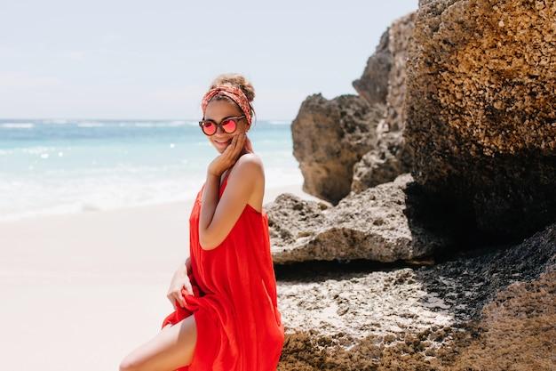 Modieus meisje in het rode de zomerkleding stellen met rotsen. portret van enthousiaste blanke dame genieten van uitzicht op de natuur op het strand.