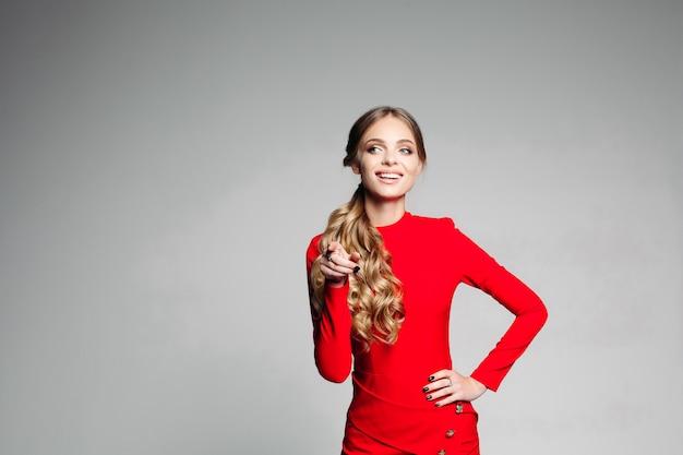 Modieus meisje in het rode dressposing bij camera met hand op heupen.