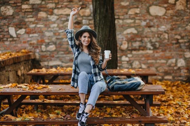 Modieus meisje in korte blauwe spijkerbroek zit met kopje koffie voor oud gebouw