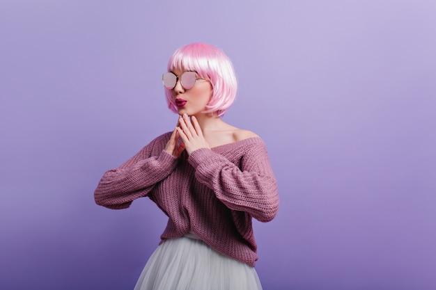 Modieus meisje in roze peruke dansen met plezier. fascinerende jonge vrouw in zonnebril en wollen trui grappige poseren op paarse muur.
