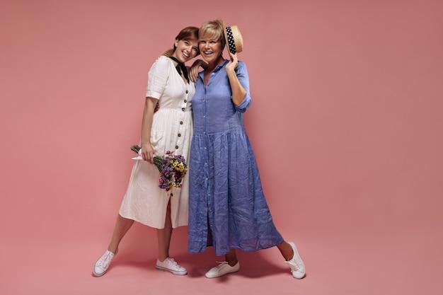 Modieus meisje in witte jurk en sneakers met wilde bloemen en lachend met blonde dame in blauwe outfit en strooien hoed op roze achtergrond.