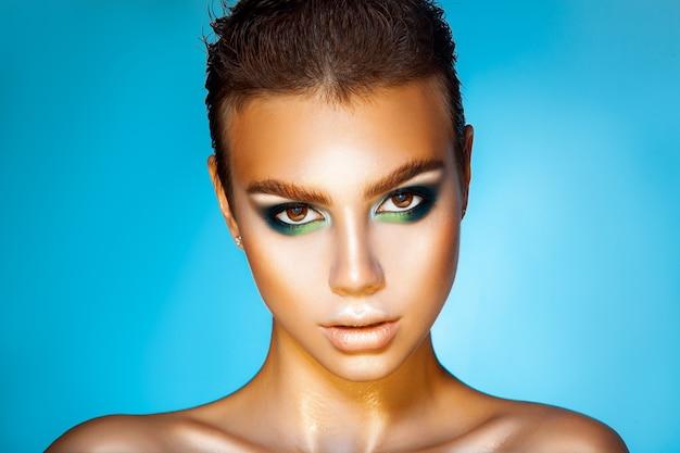 Modieus meisje met groene kleurenmake-up en kort kapsel op blauwe achtergrondstudi