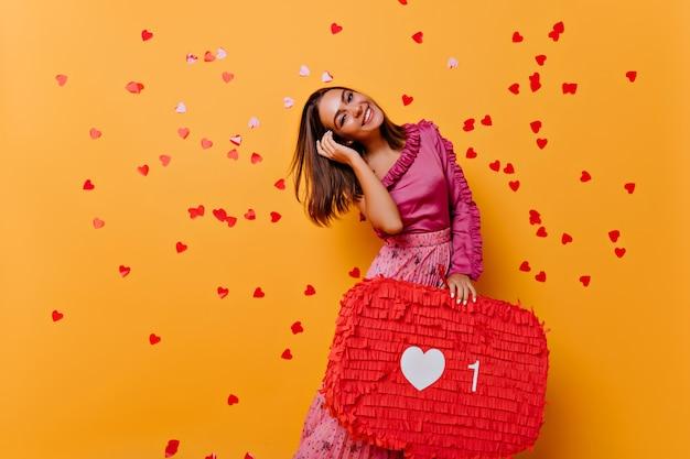 Modieus meisje met steil haar dat van sociale netwerken geniet. indoor portret van extatische lachende vrouw geïsoleerd op oranje.