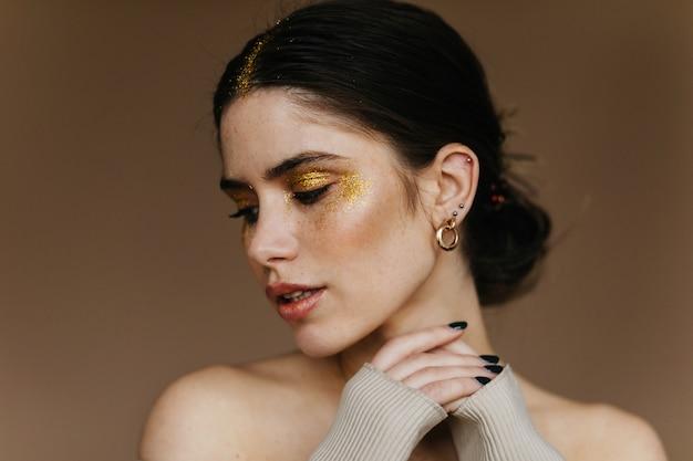 Modieus meisje met trendy oorbellen chillen. foto van blije donkerbruine dame met partijmake-up.