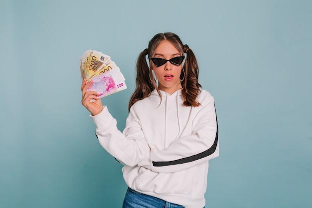 Modieus meisje met verzameld haar dat een zwarte zonnebril en een witte trui draagt die met een prop geld op geïsoleerde muur stelt