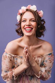 Modieus meisje poseren in romantische jurk lachen. fascinerend vrouwelijk model met krullen in een bloemencirkel die positieve emoties uitdrukt.