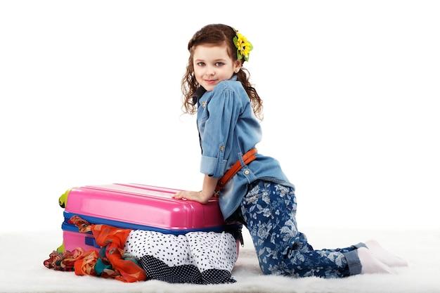 Modieus meisje sluit de koffer met kleren