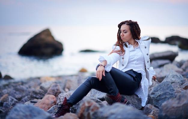 Modieus meisje van dreadlocks gekleed in een witte jas en een zwart lederen broek poseren in de buurt van zee in de avond