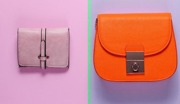 Modieus minimalisme. kleine oranje tas, lederen portemonnee op een gekleurde papieren achtergrond. bovenaanzicht