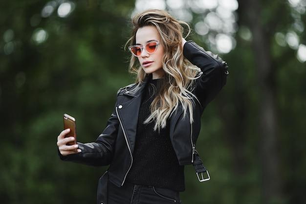 Modieus mooi en sensueel blond modelmeisje in zwart leerjasje, in jeans en het stijlvolle zonnebril neemt een selfie op haar smartphone en poseert buiten in de stadsstraat