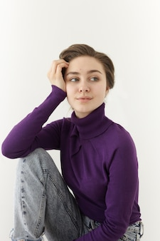 Modieus mooi jong vrouwelijk model draagt violet coltrui met lange mouwen en flodderige spijkerbroek die zich voordeed op witte muur, elleboog op haar knie leunend en zijwaarts op zoek