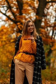 Modieus mooi lachend meisje in stijlvolle herfstkleren loopt in een gouden herfstpark met geel gebladerte