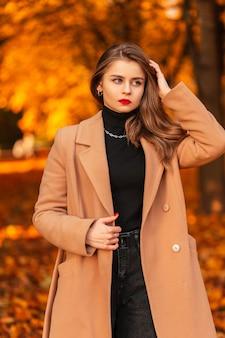 Modieus mooi meisje met rode lippen in een stijlvolle beige jas met een trui loopt door een natuur met bomen en gekleurd herfstgebladerte