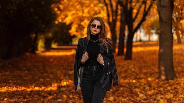 Modieus mooi meisje met vintage zonnebril in trendy zwarte kleding met een modeblazer, trui en spijkerbroek lopen in een herfstpark met oranje herfstbladeren