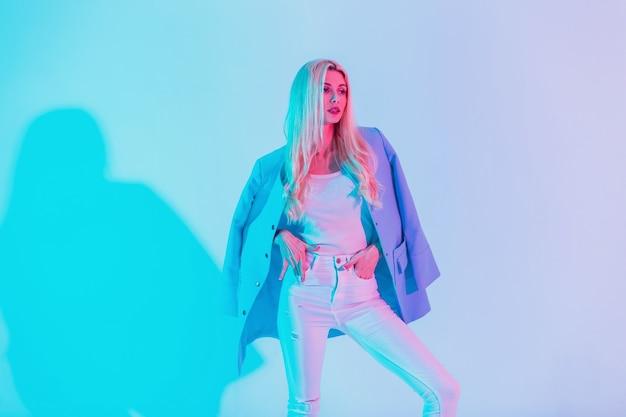 Modieus mooi zakenmeisje in witte stijlvolle glamouroutfit met blauwe blazer op pastelkleurige neonroze lichten