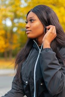 Modieus mooi zwart vrouwenmodel met stijlvol casual jasje in park met gekleurd herfstgebladerte