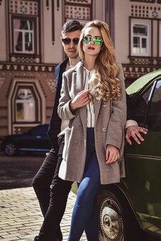 Modieus paar in zonnebril staan op straat in de buurt van de auto