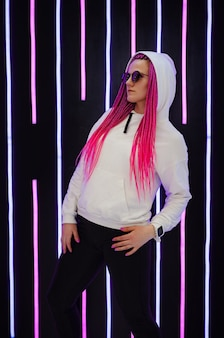 Modieus portret van een jonge elegante vrouw die een zonnebril draagt met trendy roze vlechten en neonlichten
