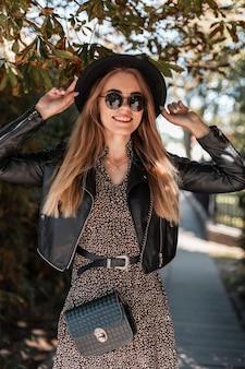 Modieus portret van een mooie jonge vrouw met zonnebril in een stijlvolle casual look kleding met een handtas en een hoed loopt in het park op een zonnige herfstdag