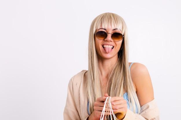 Modieus portret van een slanke blonde met lang haar in een lichtblauwe jurk en een corduroy overhemd