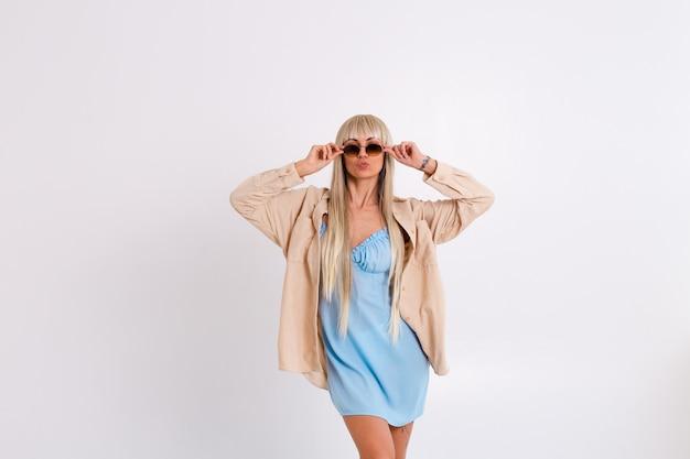 Modieus portret van een slanke blondine met lang chique haar in een lichtblauwe jurk en een corduroy overhemd