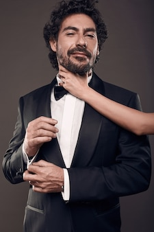 Modieus portret van elegant sexy paar in studio. brutale man in pak met vrouw hand aanraken van zijn gezicht op donkere achtergrond
