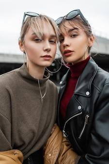 Modieus portret van mooie jonge vrouwenzusters met stijlvolle kleding in zwart leren jack op straat