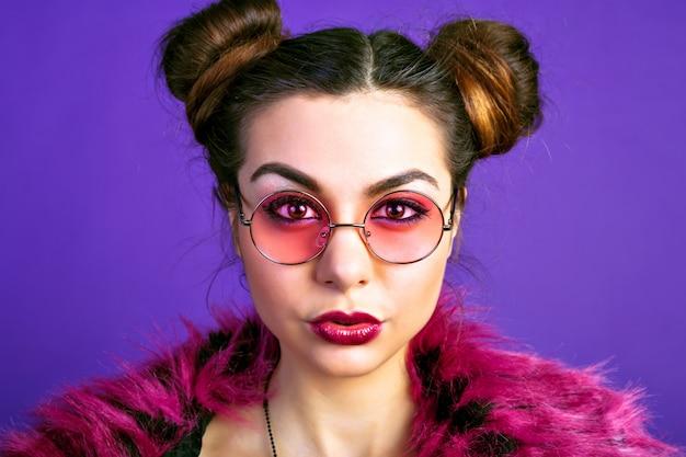 Modieus portret van vrolijke brunette vrouw, poseren in trendy wrok outfit, nepbont jas, make-up. volle sexy lippen, kus verzenden. vintage roze bril.