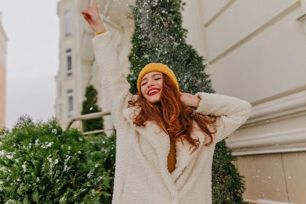 Modieus roodharig meisje poseren onder de sneeuw. buiten foto van lachende blanke vrouw genieten van winterweekend.