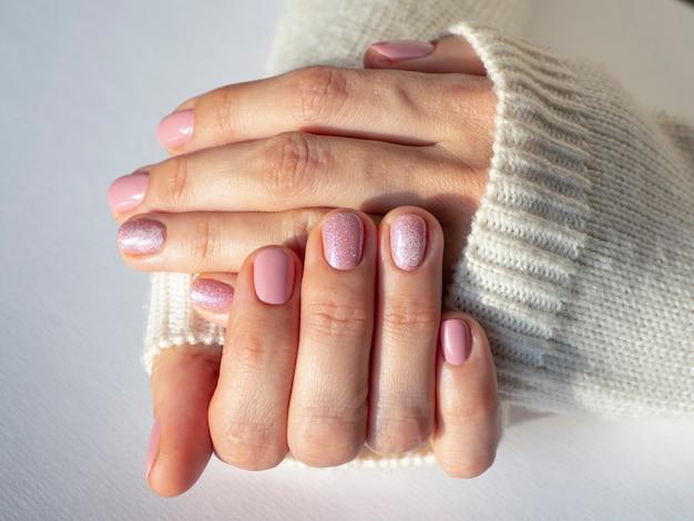 Modieus roze manicure-ontwerp in de hand. detailopname.