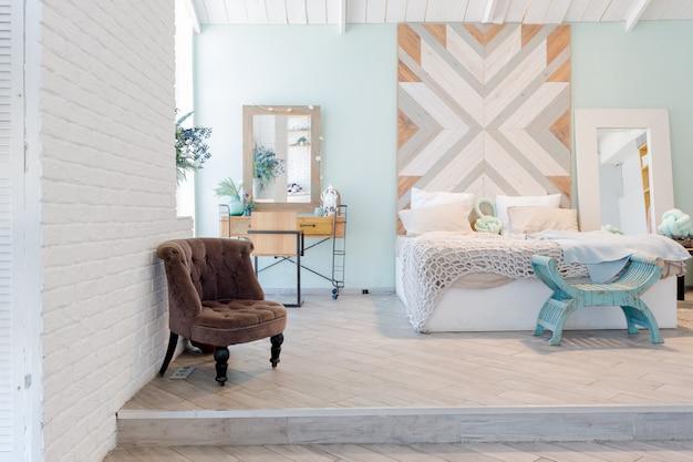 Modieus ruim appartement met een stijlvol design in groene, grijze en witte pastelkleuren met groot raam en decoratieve wanden. slaapkamer en keukenruimte