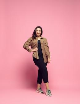 Modieus, stijlvol. jonge vrouw in vrijetijdskleding op roze.
