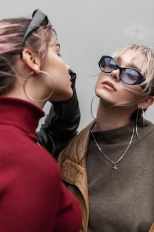 Modieus stijlvol modeportret van mooie jonge meisjes in een modieuze outfit met een bril, een trui en een leren jas in de stad. stedelijke kledingstijl voor dames