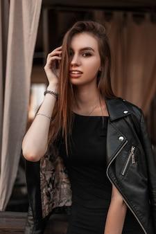 Modieus vrij jong vrouwenmodel in een vintage zwart leerjasje in een zwarte stijlvolle jurk maakt haar binnenshuis recht. mooi modern meisje in trendy kleding poseren in een café. lente stijl.