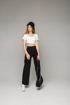 Modieus vrouwelijk model in zwarte pet, wit t-shirt, zwarte broek met tas