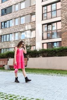 Modieus vrouwenmodel in roze jurk en zonnebril poserend tegen de achtergrond van de stadsstraatcatalogus