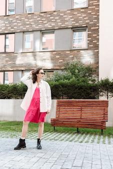 Modieus vrouwenmodel poseert buiten op de achtergrond van de stadsstraat in de nieuwe kledingcollectie