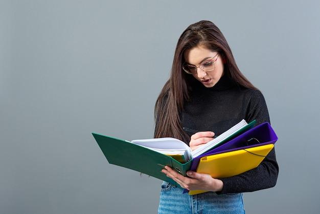 Modieus wijfje dat kleurrijke omslagen met documenten houdt