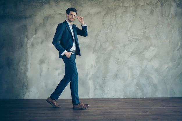 Modieus zakenman poseren tegen de grijze muur