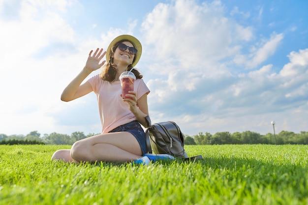 Modieus zomerportret van tienermeisje in hoed met drankje zittend groen gras, blauwe lucht in de wolken,