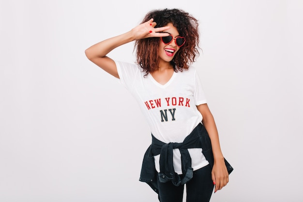 Modieus zwart meisje in wit t-shirt poseren met vredesteken en grote glimlach staan. indoor portret van vrij vrouwelijk model met afrikaanse kapsel lachen en dansen.