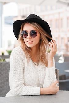 Modieuze aantrekkelijke jonge hipster vrouw in een stijlvolle gebreide trui in modieuze zonnebril in een elegante zwarte hoed, zittend in een café op een zonnige zomerdag. mooi meisje blond.