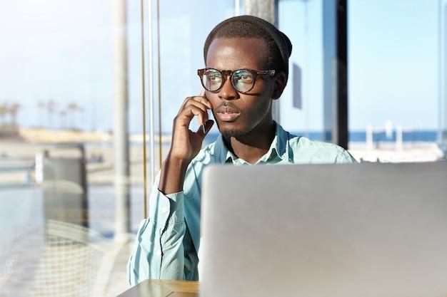 Modieuze aantrekkelijke jonge ondernemer die telefoongesprek heeft