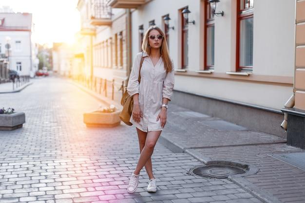 Modieuze aantrekkelijke jonge vrouw in een stijlvolle zonnebril in een stijlvolle witte zomerjurk in witte sneakers met een stijlvolle lederen tas poseren op een oude straat in de stad op een zonnige dag. leuk stadsmeisje