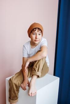 Modieuze aantrekkelijke tweenjongen met donker haar in hoedenzitting op witte kubus in studio, jonge geitjes modellering