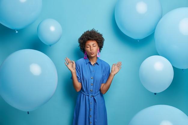 Modieuze aantrekkelijke vrouw heft handen op en houdt de lippen afgerond, krijgt plezier en poseert tegen blauwe muur met ballonnen, poseert voor fotoshoot in ingerichte kamer, draagt mooie lange jurk