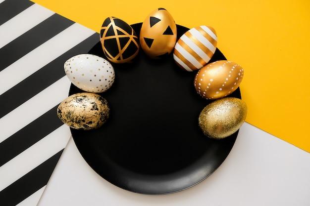 Modieuze achtergrond met gouden verfraaide eieren van pasen op zwarte plaat.