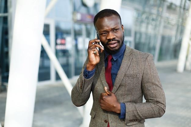 Modieuze afrikaanse amerikaanse zwarte zakenmanbesprekingen op zijn smartphone