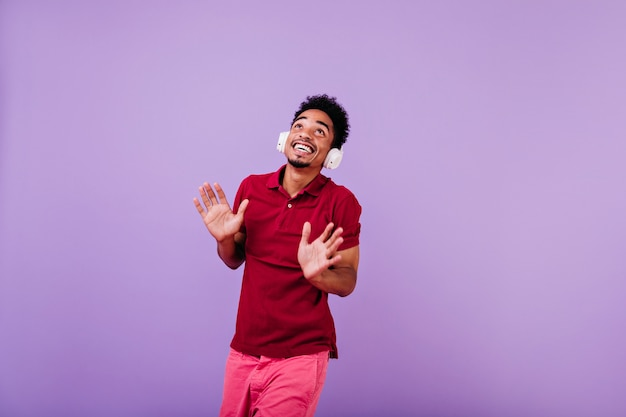 Modieuze afrikaanse man in trendy rode kleding opzoeken. verfijnde man met koptelefoon die voor de gek houdt